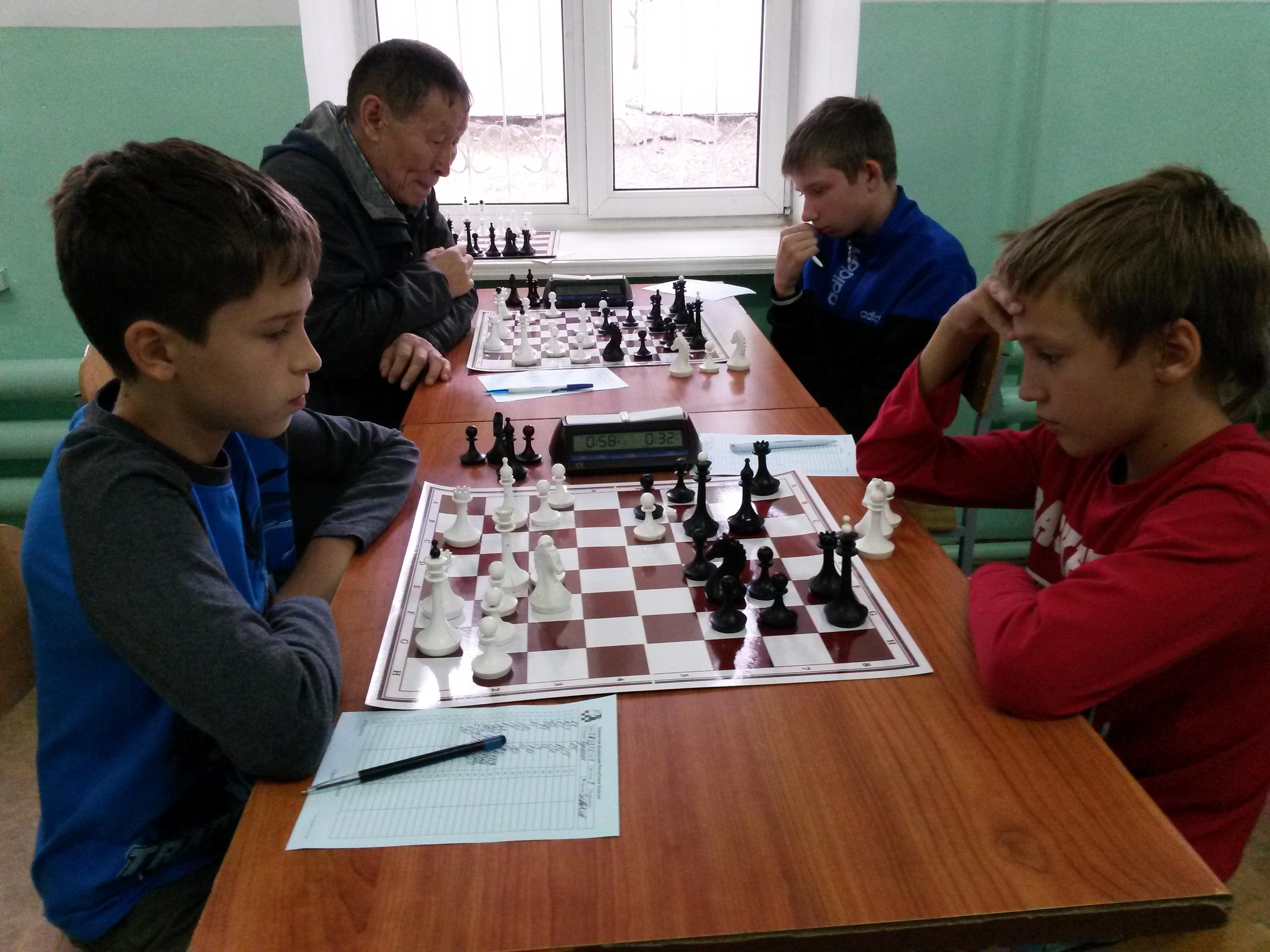 На переднем плане партия Гунькин-Завьялов.Сильнейшие шахматисты Хакасии по своим возрастам сыграли вничью.