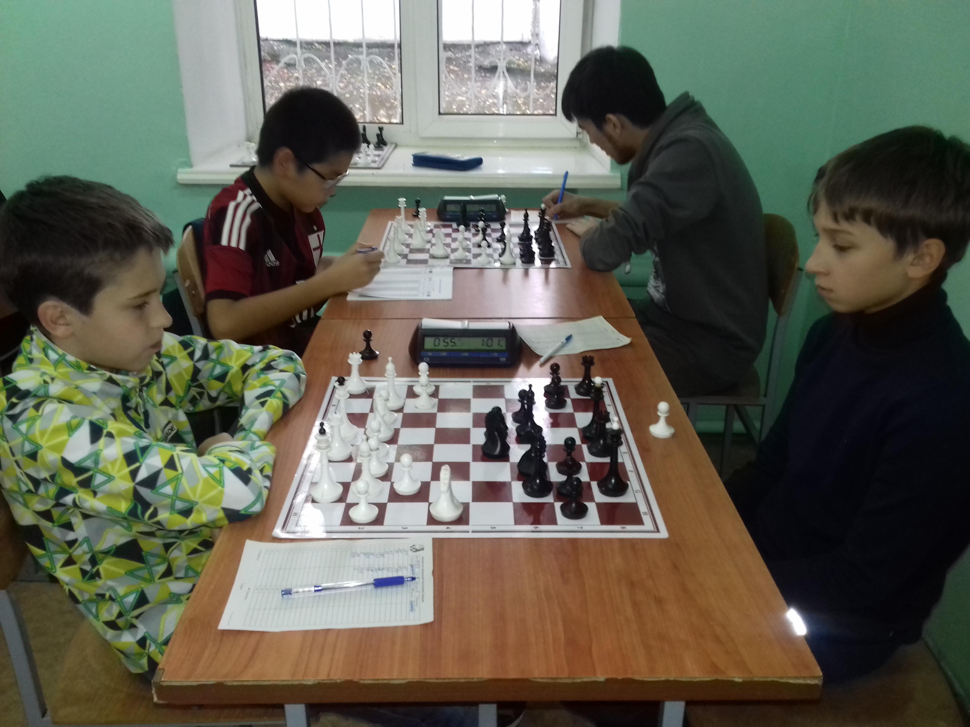 На дальнем плане Канзычаков побеждает Самбурского, на переднем плане Гунькин и Сейбель играют вничью.